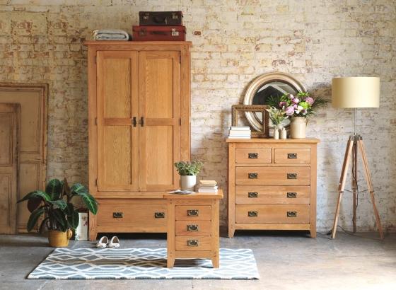 Oakland Bedroom Set, Brick walls, grey rug, Round Mirror, Tripod Lamp, Vintage Suitcases