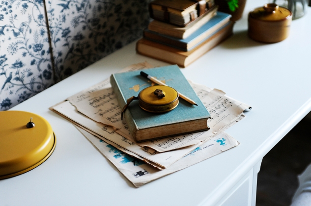 Book on dressing table, music sheets, mustard tap measure