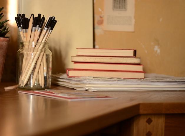Oak desk, home office, pencils, books, paper