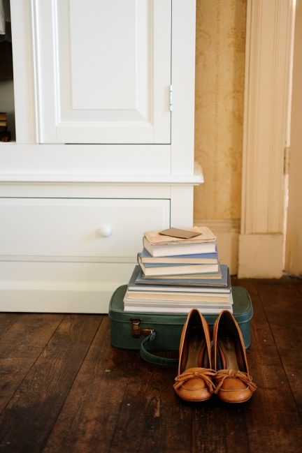 Stack of blue books, on top of suitcase