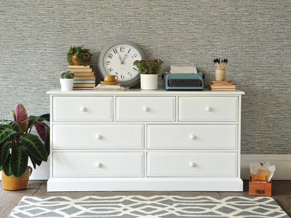 White painted bedroom furniture, grey clock, geometric rug, typewriter, pencils, books