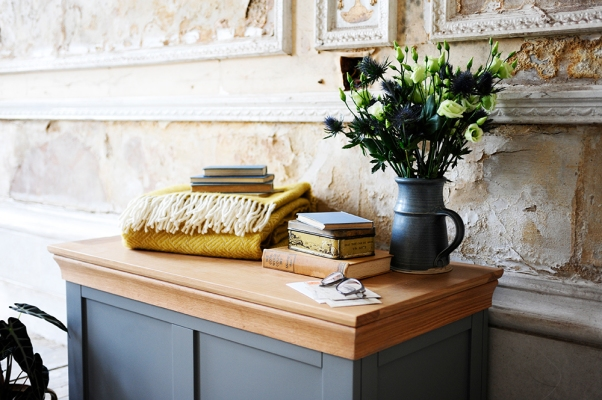 Grey blanket box, mustard throw, blue ceramic jug, thistles