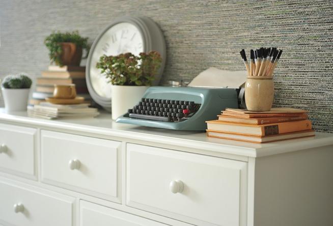 White bedroom furniture, blue typewriter, grey walls