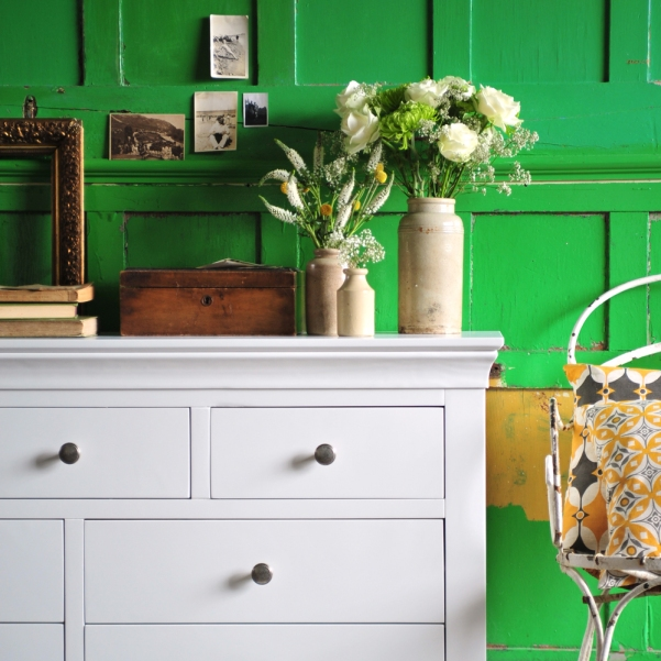 white bedroom furniture, green wall, gold frames, books, vintage vases