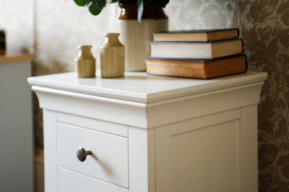 White bedside table, white furniture, vintage wallpaper, books, earthernware