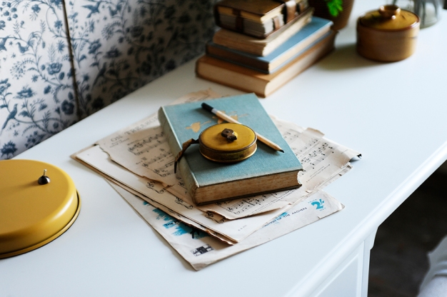 White desk, yellow, lamp, blue book, music paper